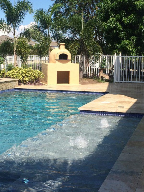 A Forno Nardona wood fired pizza oven situated by a pool in Tampa, FL.
