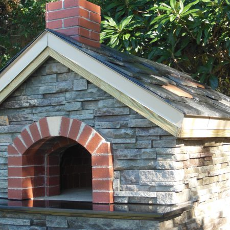 Custom home pizza oven with a brick dome, stone finish, and unique roof.