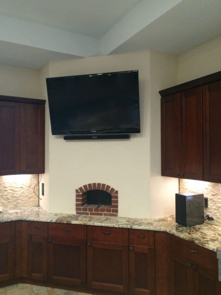 Forno Nardona oven installed inside a kitchen with a TV mounted above it.