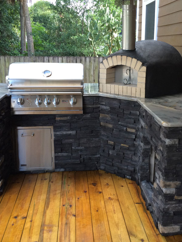 An outdoor kitchen complete with a Forno Nardona wood-fired pizza oven and a Lion BBQ Grill.
