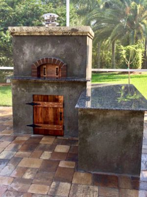 An outdoor kitchen with a custom wood-fired pizza oven built and installed by Forno Nardona in Tampa, FL.