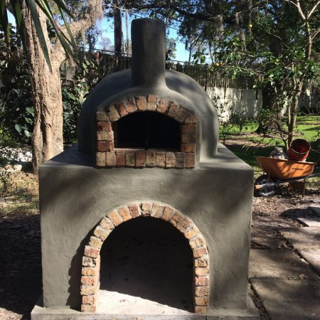 Residential brick dome pizza oven with a cement finish.