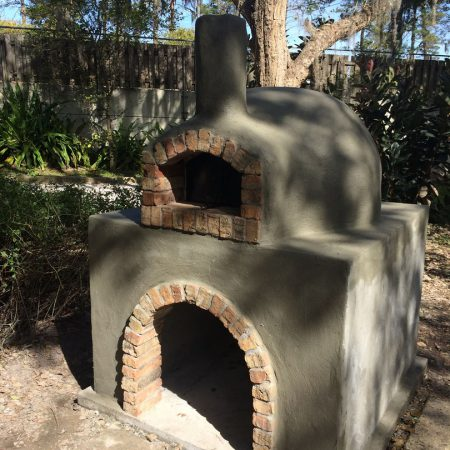 Outdoor wood-fired pizza oven with a natural cement finish.