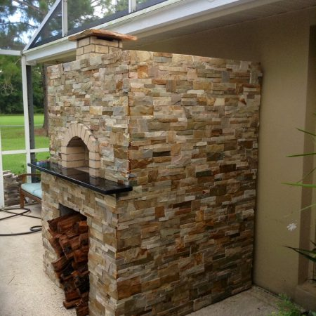 Brick dome pizza oven complete with stone a stone finish and wood storage.