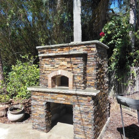 Large outdoor wood fired pizza oven with a light stone finish.
