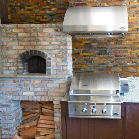 An outdoor kitchen with a brick pizza oven.