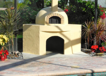A Forno Nardona crafted wood-fired pizza oven sits outside beside a pool in Tampa, Florida.