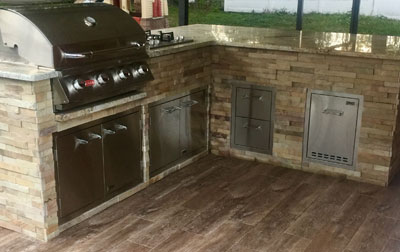 An outdoor kitchen equipped with a Lion BBQ Grill.
