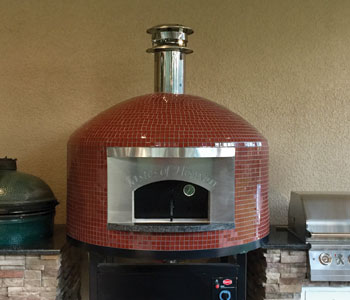 An outdoor pizza oven with red glass tiling and a brick-dome