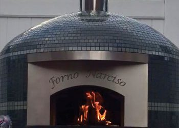 An outdoor pizza oven with a glass tile finish and a custom engraving