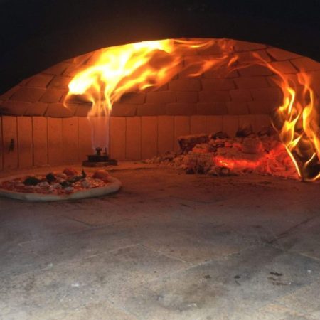 Pizza cooking inside a traditional pizza oven by rolling fire with gas assistance