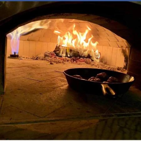 Food being cooked inside a brick dome pizza oven