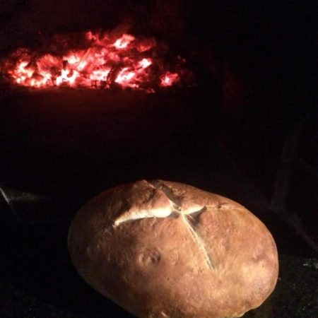 Bread being baked in a brick dome oven