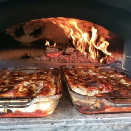 Lasagna being cooked inside a wood-fired pizza oven with a brick dome interior
