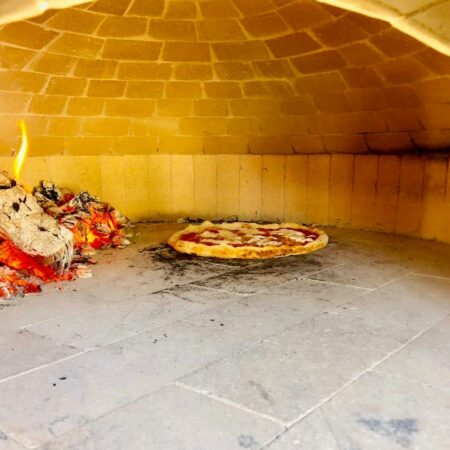 Forno Nardana brick oven dome with a pizza cooking inside of it.