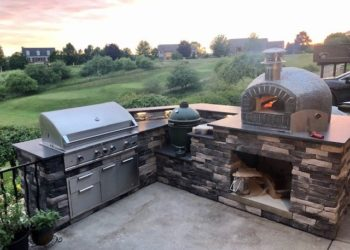 Forno Nardona Rustico oven on corner stoned base with granite countertop with a grand back yard view.